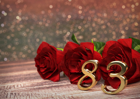 83rd: birthday concept with red roses on wooden desk. 3D render - eighty-third birthday. 83rd