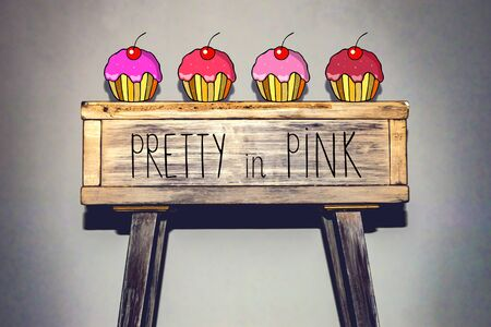 pretty in pink - phrase. cupcakes with pink icing on a wooden table