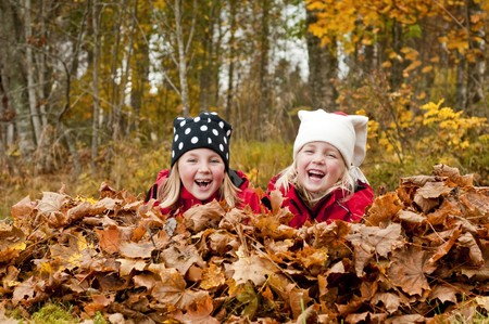 lying in leaves: Children lying in heap of autumn leaves laughing. Stock Photo