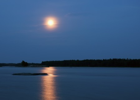 Full moon reflecting in water in the night. photo