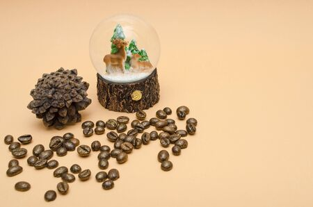 pine cone, glass bowl with three Christmas trees and two deers, sprinkled roasted gilded coffee beans on pastellgelb background copy space 免版税图像