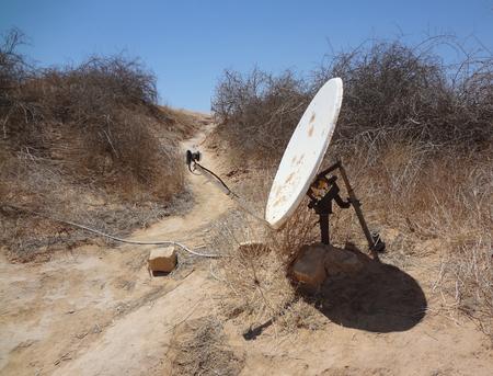 Satellite dish with actuator, in the desert of Tunisia. Unusual antenna installationin the sands of the desert.
