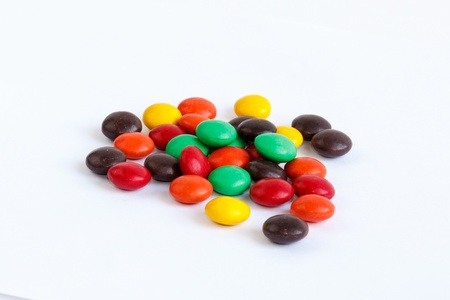 Multicoloured chocolate drops on a white background photo