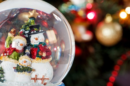 glass globe: Snow globe with happy snowman family on christmas tree blured background