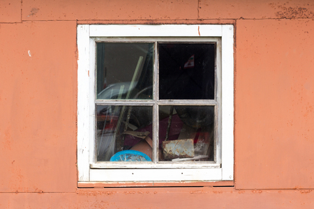 Rustic vintage window with broken glass on red wall