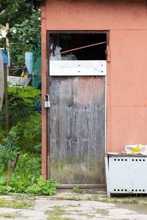 Old rustic wooden door on facade of red barn