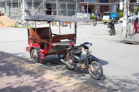 KAMPOT, CAMPBODIA - 21 NOVEMBER 2011: Cambodian red tuk-tuk parked on the city street on 21st of November 2015 in Kampot, Cambodia. Tuk-Tuk is the most popular transport in Cambodia