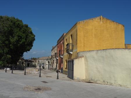 cast off: Pastel coloured houses on the square of Tratalias Vecchia, Sardinia Stock Photo
