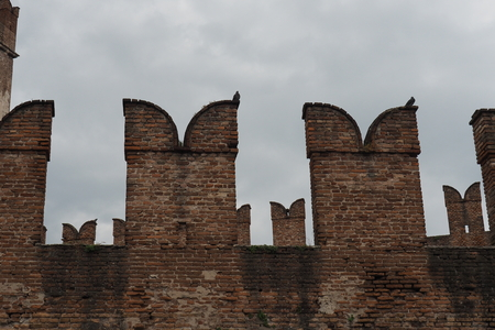 grey  sky: Close-up of the battlements of the Castelvecchio in Verona, Italy, with two pigeons, against a dramatic grey sky. Stock Photo