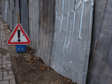 danger ahead: A damaged triangular road sign with an exclamation mark, warning of danger ahead, next to a corrugated iron fence
