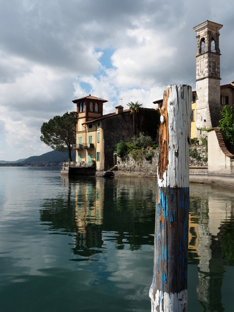 lakefront: The Perdore church and lakefront under a dramatic cloudy sky, reflected in the Iseo Lake, in Lombardy, Italy