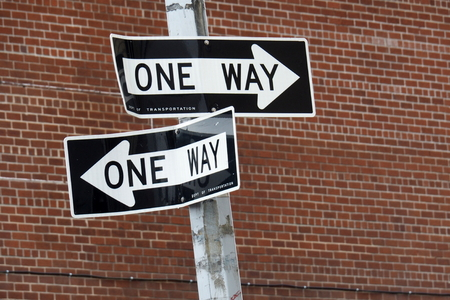 diverging: Two One Way Signs connected to one pole, seemingly pointing in opposite directions, in front of a red brick wall Stock Photo
