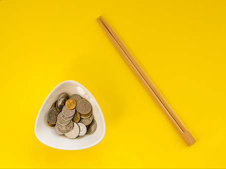 A lot of coins in a white bowl and wooden chopsticks on a yellow background. The concept of the inability to eat money and greed. Flat lay, top view. Banco de Imagens