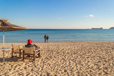 Winter sea beach and calm sea on a sunny day. A lonely  elderly woman sits in a deck chair facing the sea. A loving couple stands by the water. Cargo ship in the distance on the horizon. The concept of the transience of time.