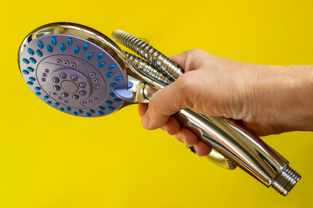 Female hand holding shower head and flexible hose on a yellow background. Handheld shower head with with function switch. Modern shower equipment. Plumbing works.