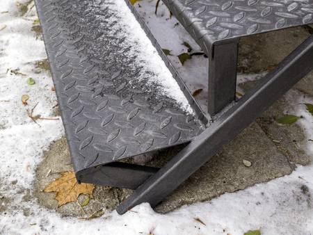 Corrugated steps of the iron staircase powdered with the first snow close up