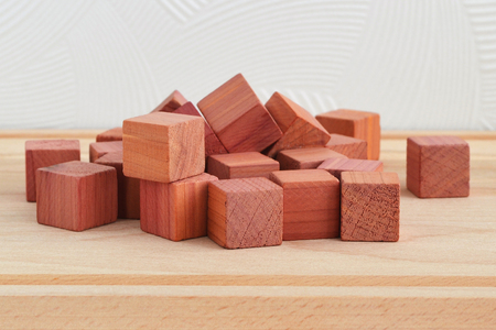Fragrant wardrobe freshener cubes made of natural pencil cedar wood, close up on wooden background, front view