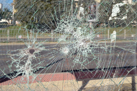 Close up of broken safety glass with many cracks at a bus stop on a city street on a day