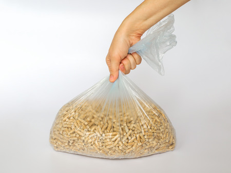 Woman hand holds a plastic cellophane bag with wooden pellets on white background. Alternative biofuel from sawdust for burning in furnaces and stoves. Cat and hamster litter.