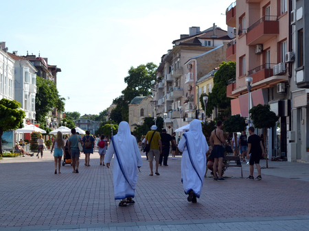 Two missionaries of charity walk along a pedestrian street in the tourist part of the Varna city with many small shops and street cafes. Editorial