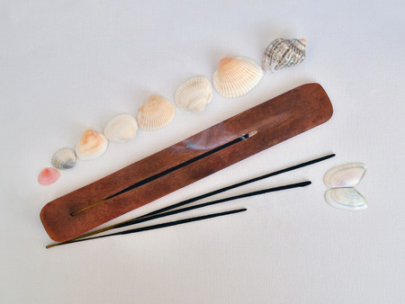 Incense stick is in a stand and smoldering, above it rises fragrant smoke. Sea shells and a few more incense sticks are picturesquely arranged around the stand on a pastel textile background, top view.