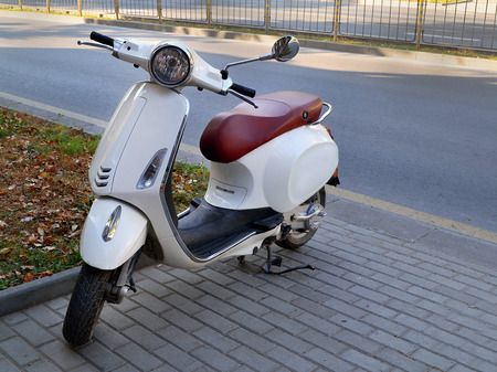 Varna, Bulgaria, August 2018. White colored scooter with red leather saddle parked on the street on a summer day
