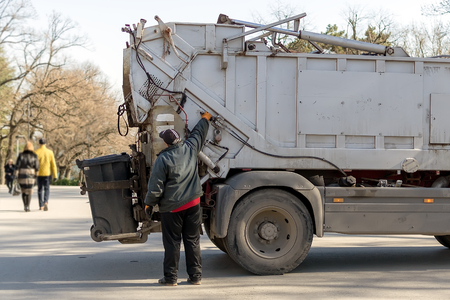 Varna, Bulgaria, February 28, 2019. The garbage truck operator controls the emptying of the garbage bin. Loading rubbish into a garbage truck in a public park on a spring day. Waste disposal and cleanliness. City life.