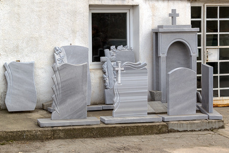 Small private firm produces tombstones and exhibites samples of its products outdoors along the sidewalk.