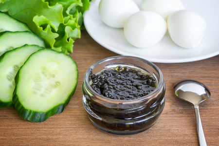 Natural black caviar in small glass jar, few boiled quail eggs, some slices of cucunmber and fresh green lettuce on a brown wooden background. Sturgeon caviar, fish delicacy.
