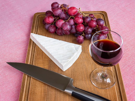 Whole piece of Brie cheese, glass of red wine, red sweet grapes and chef knife on a brown wooden cutting board. Soft cheese covered with edible white mold. Food still life of on a pink tablecloth.