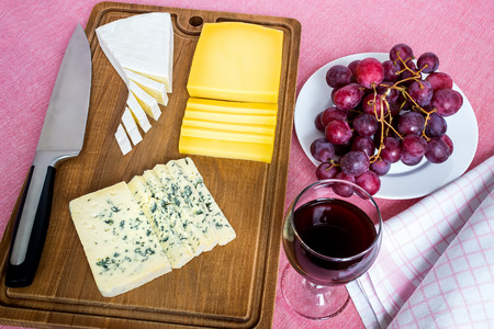 Glass of red wine, sweet red grapes on white plate and tree types of sliced cheese on brown wooden cutting board. Cheeses covered with edible white and blue mold. Top view. Food still life on a pink tablecloth. Banco de Imagens