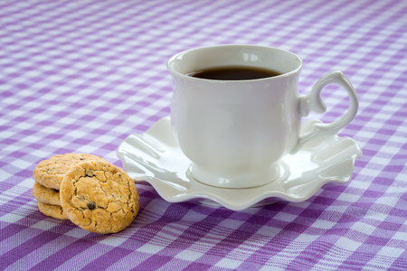 White porcelain saucer with wavy edge with cup of tea on it. Sweet oat cookies with pieces of dark chocolate. Cup of tea and cookies on a checkered white purple tablecloth. High-calorie breakfast. Reklamní fotografie