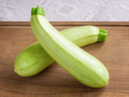 Two fresh green courgettes or zucchini criss-cross on a brown wooden cutting board. Cook at home. Fresh vegetables, vegetarianism and healthy eating. Close-up. Stok Fotoğraf