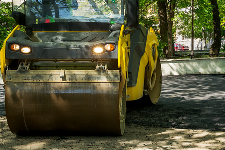 An asphalt tamping roller works in a public park on a sunny spring day. Repair of asphalt roads. Asphalt paving and urban improvement. Stock Photo