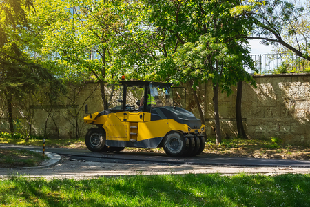 One asphalt tamping roller works in a public park on a sunny spring day. Repair of asphalt roads. Asphalt paving and urban improvement. Stock Photo