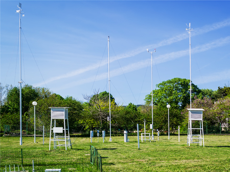 Green lawn with meteorological instruments for measuring the wind speed, temperature and humidity on a sunny summer day.