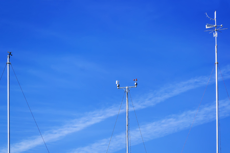 Meteorological instruments for measuring the wind speed, temperature and humidity on poles against a blue sky. Stock fotó