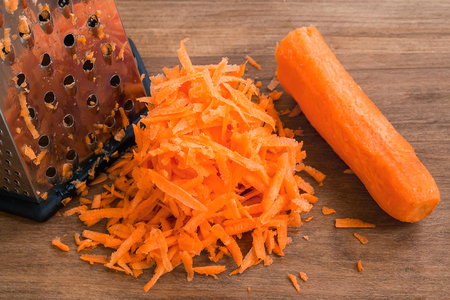 Fresh raw grated carrot on a brown wooden background. The concept of healthy eating, vegetarian food and cook at home. Close-up.