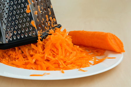 Juicy raw grated carrot on a white plate. The concept of healthy eating, vegetarian food and cook at home. Close-up.