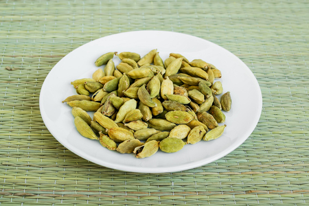 A lot of dry cardamom seeds on a white saucer on a green table mat made of natural plant fibers. Natural food spices and seasonings. Tasty eating.