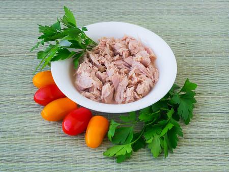 Filete de atún en conserva en cuenco de porcelana blanca, perejil y unos tomates cherry sobre un tapete verde de fibras vegetales naturales. Mariscos, alimentación saludable. Atún enlatado para ensaladas.