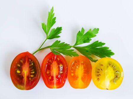 Tomates cherry cortados por la mitad y una ramita de perejil sobre un fondo blanco. Tomates cherry multicolores. Verduras, alimentación vegetariana y saludable. Vista superior.