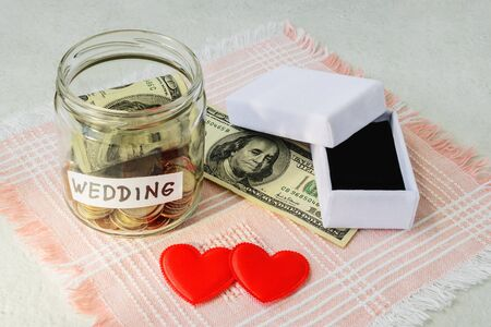 Wedding word, coins and dollar bill in a glass jar near two silk hearts and empty white wedding ring box on a pink fringed napkin. Saving money for wedding concept. Planning for future expenses and to make targeted savings. Stock Photo