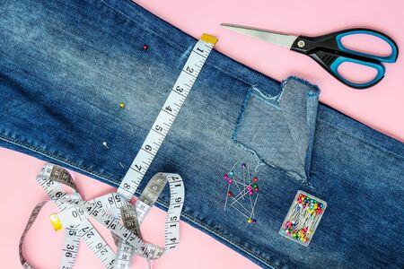 Blue jeans with a large hole on a pant leg below the knee are folded in half and pinned with tailor pins. White tailor tape with centimeters and inches at a cut line and scissors on a pink background. Flat lay. Top view.