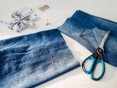 Pant leg with a large hole cut off with scissors from a blue jeans folded in a half. Making denim shorts. On a white background.