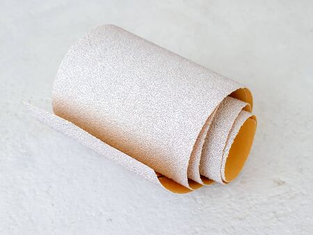 Small roll of extra coarse aluminum oxide sandpaper on a white rough textured background. Abrasive paper for dry sanding. Processing wood and metals, furniture production. Close-up.