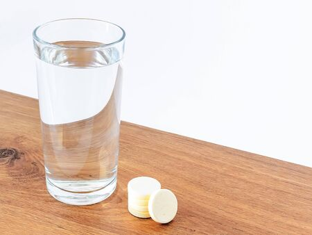 Glass of drinking water and some soluble effervescent vitamin pills on a wooden background with white copy space. Vitamins and nutritional supplements. Health care and medical. Side view.
