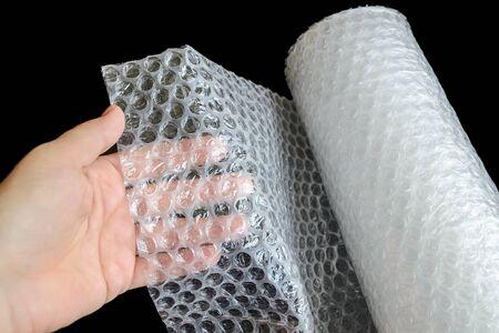 Frauenhand, die einen weißen transparenten Kunststoff auf schwarzem Hintergrund hält. Material zum Verpacken von zerbrechlichen Gegenständen für einen sicheren Transport. Ansicht von oben.