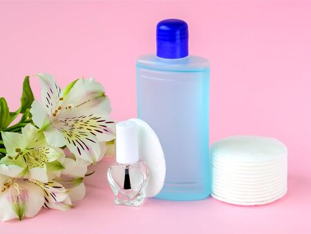 Glass bottle with colorless nail polish, plastic bottle with nail varnish remover, cotton pads and white flowers on a pastel pink background. Manicure, pedicure, nail care products. Front view. Stock Photo