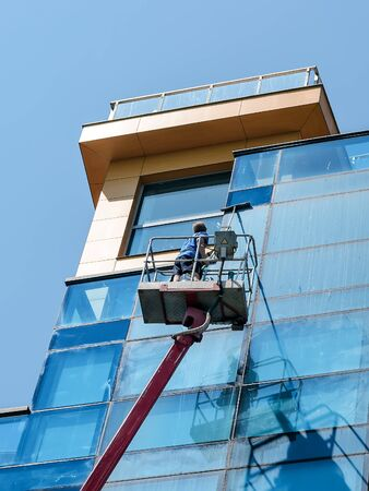Man with mop washing a blue glass wall from autotower or aerial work platform on a sunny summer day. Real people and city life. Man washes a windows from autotower. Low angle view. 版權商用圖片